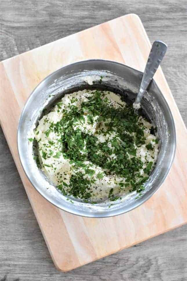 Chopped parsley on ricotta cheese mixture in a mixing bowl