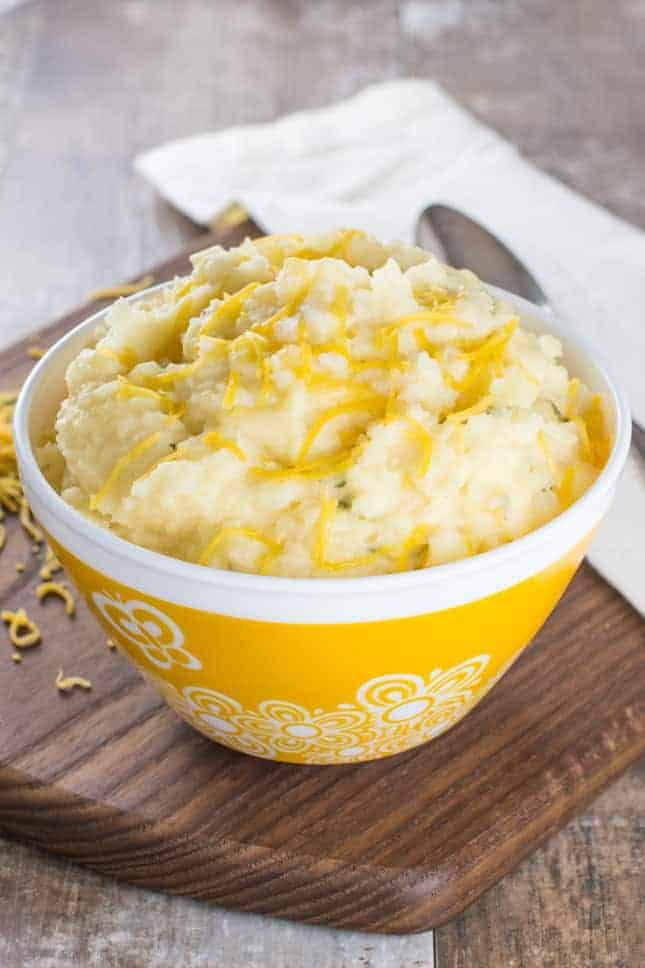 Mashed potatoes in a yellow bowl with extra cheese on top