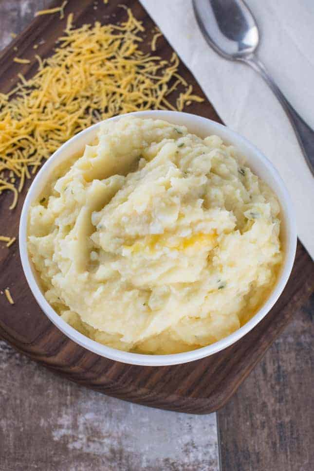 overhead of mashed potatoes in a bowl with shredded cheddar behind it