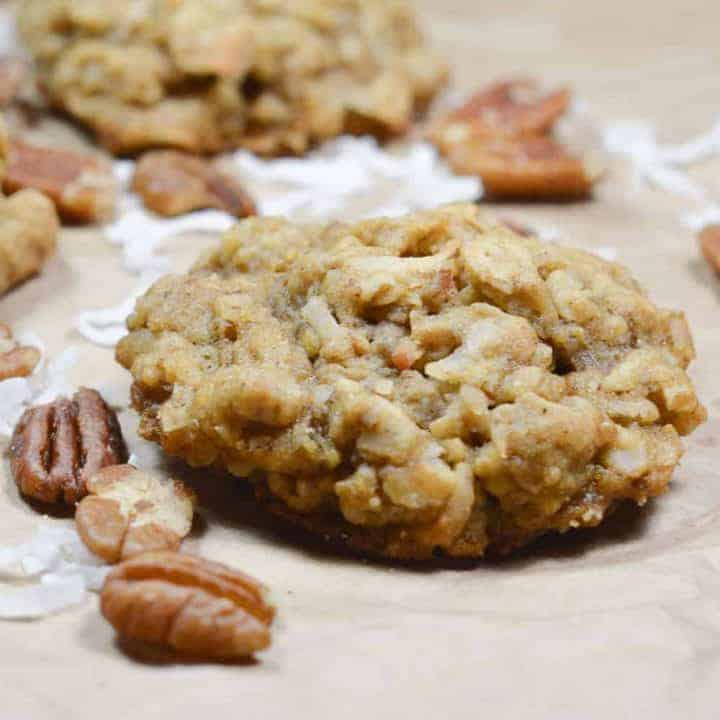 close up of one cookie with one behind it and some pecans and coconut around them