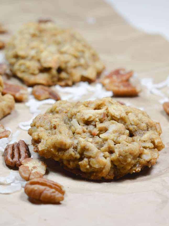 close up of an oatmeal cookie with some pecans and coconut around it and another one out of focus behind it
