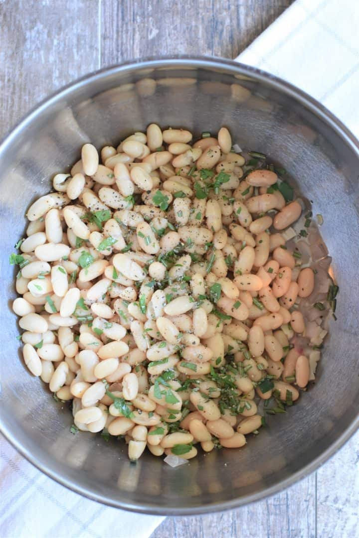 Beans and herbs added to soup pot