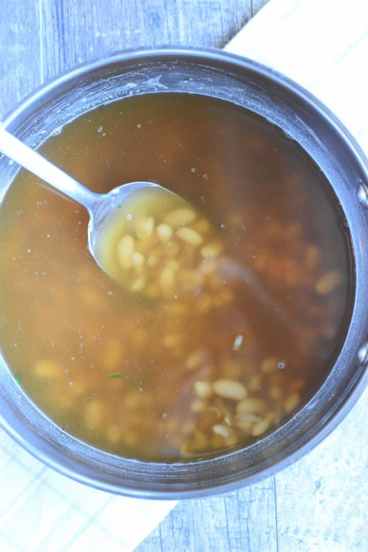 Stirring broth into the bean mixture in the soup pot