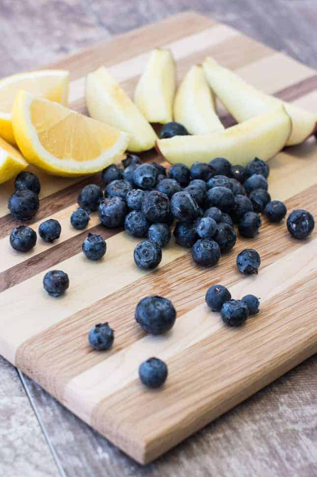 apples, blueberries and lemons on a wooden board