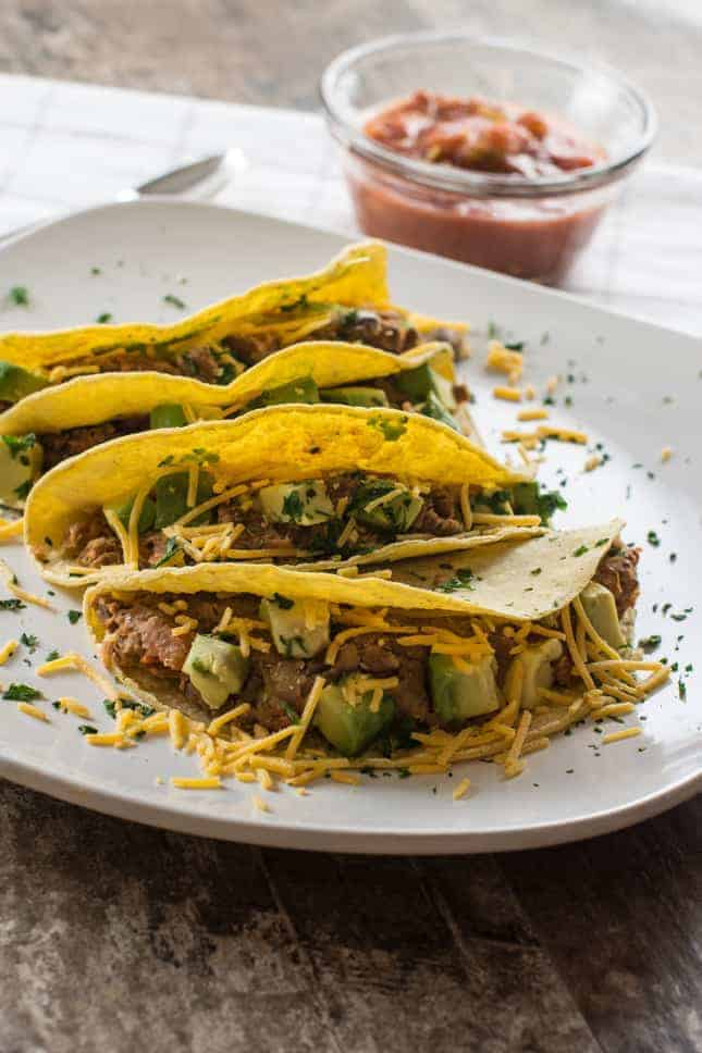 Tacos on a plate with shredded cheese and salsa in the background