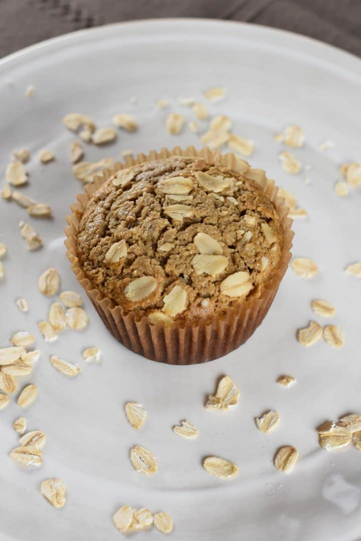 single muffin on a white plate with oats around it