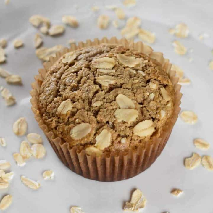 one muffin on a plate with raw oats around it
