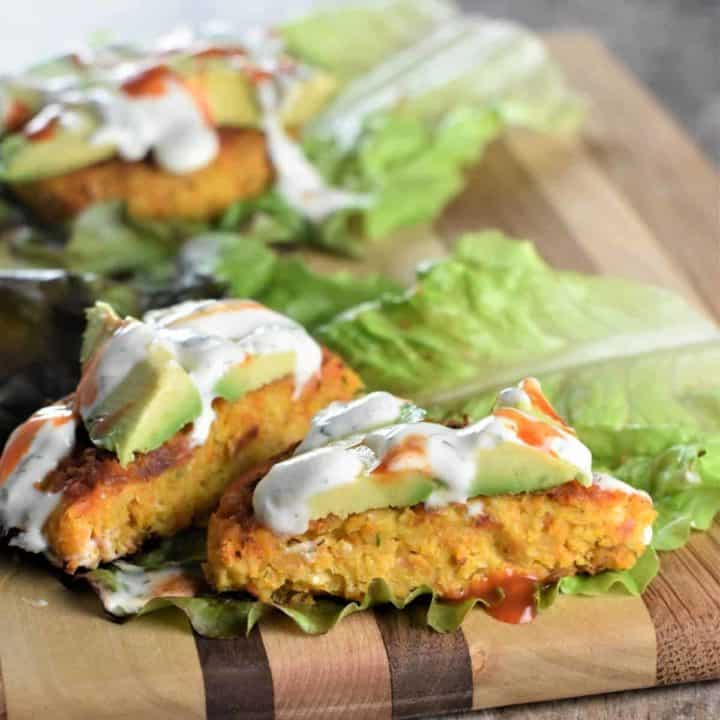 chickpea burger on lettuce and cut open to see inside with vegan ranch and avocado slices on top
