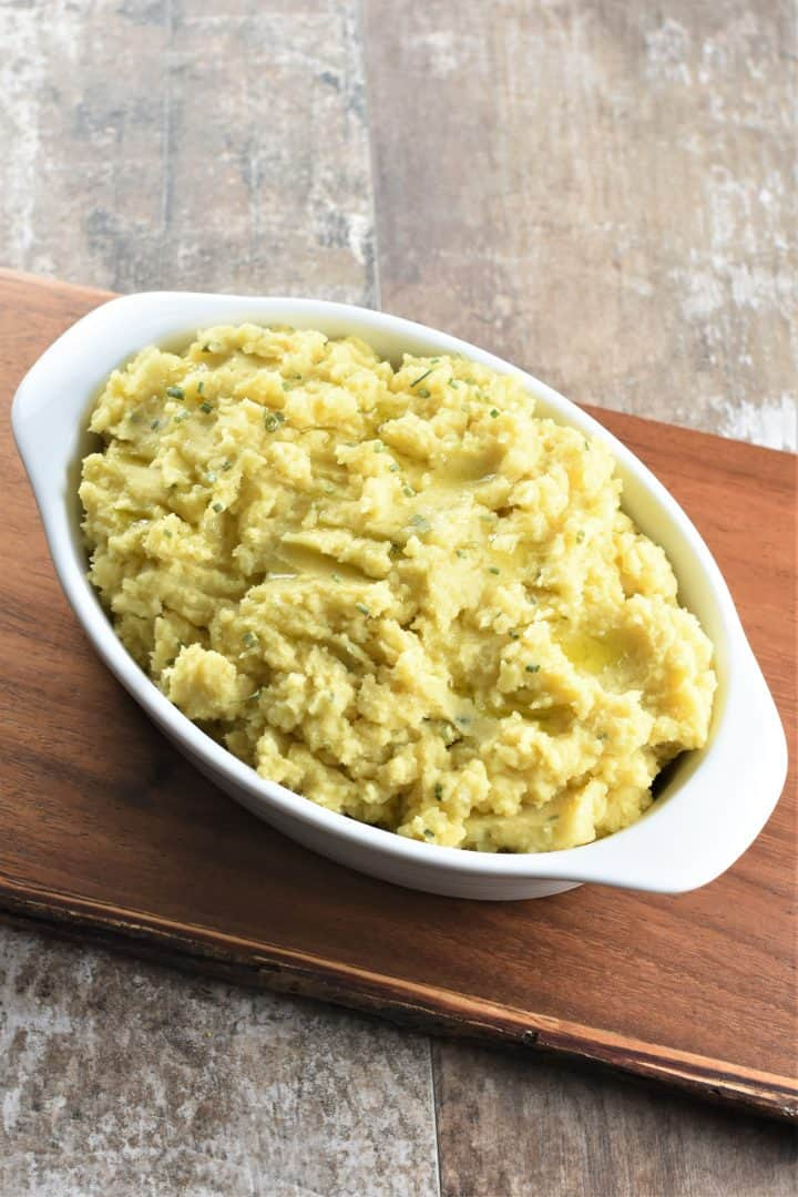 mashed potatoes in white serving bowl on wooden board