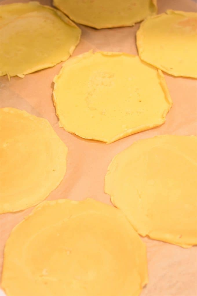 Cooked manicotti shells (crepes) placed separately on parchment paper