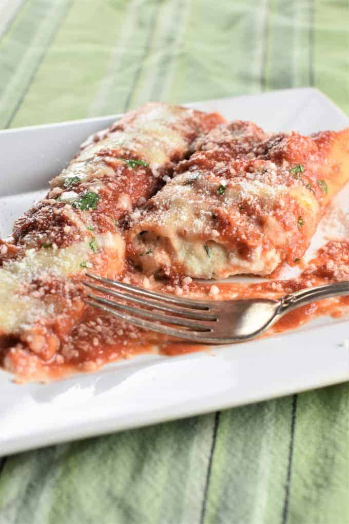 Two homemade manicotti on a plate with one cut open to reveal cheese inside and a fork on the plate