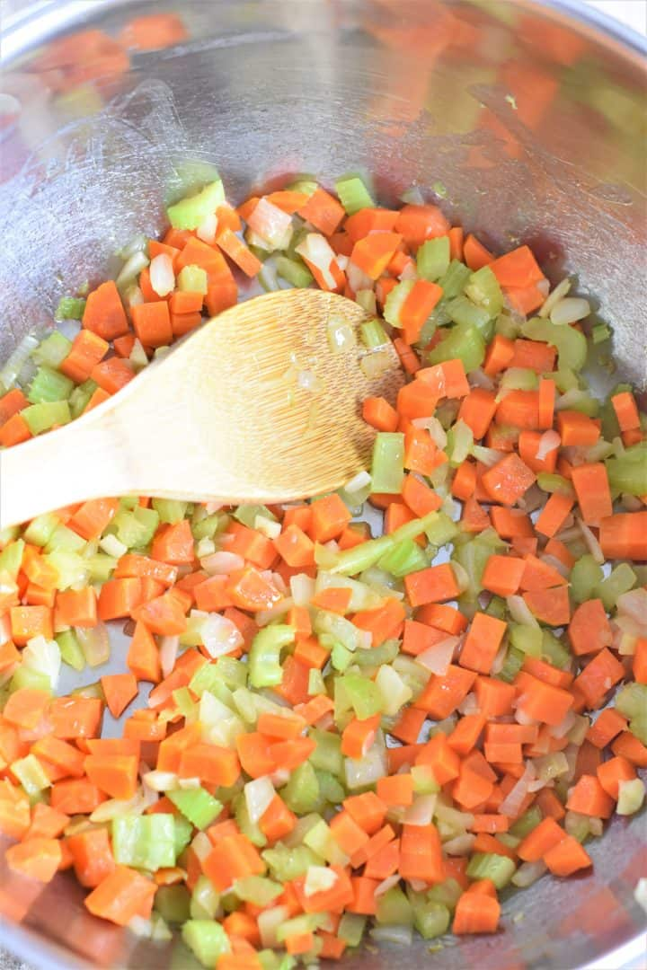 Cooking carrots, celery, onions and garlic in a soup pot