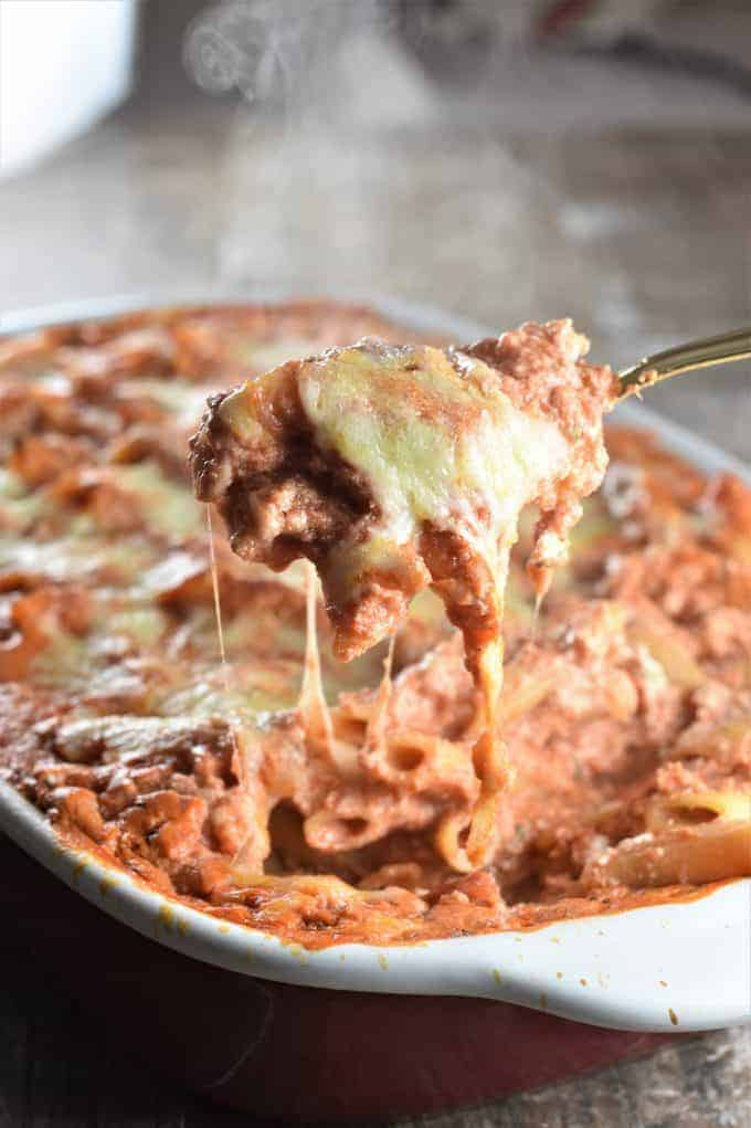 Spoon scooping baked ziti with steam