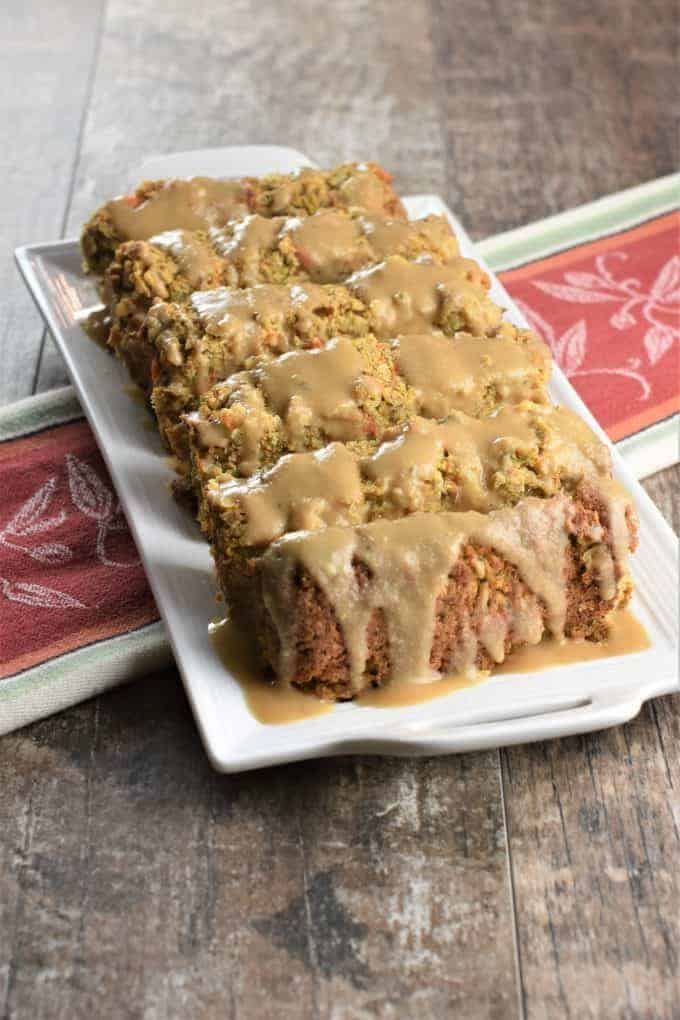 Eye level view of chickpea meatloaf on serving platter with gravy on top