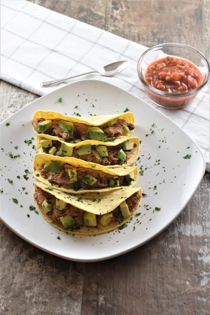 Smashed Pinto Bean Tacos on white plate with salsa in the background