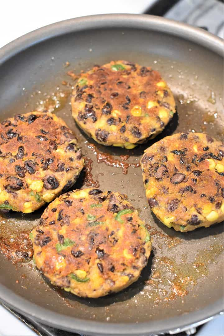 Cooking the sweet potato black bean burgers on the other side after they were flipped