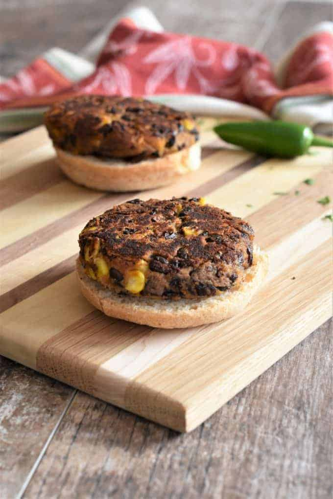 Two sweet potato black bean burgers on the bottom half of buns on a cutting board