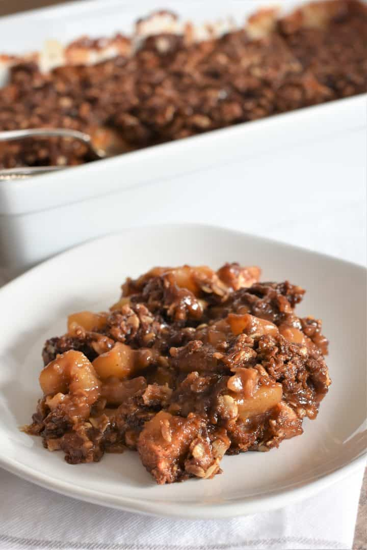 apple crisp on a plate with the baking dish with the rest in the background