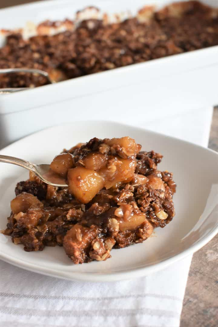 Vegan apple crisp being scooped up with a fork