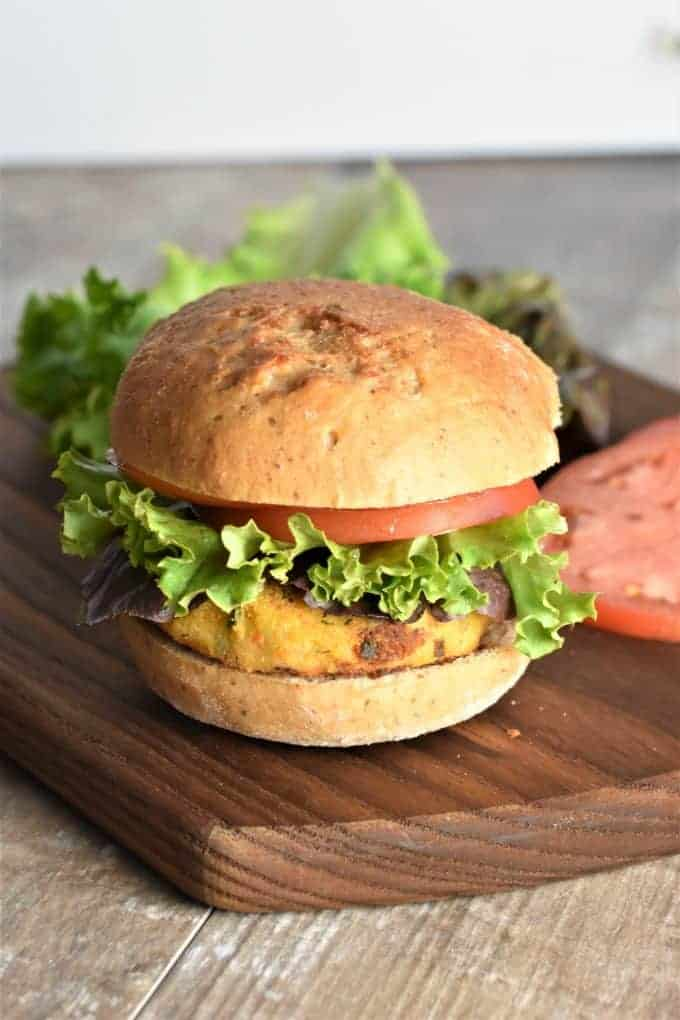 Veggie burger sitting on a wood cutting board