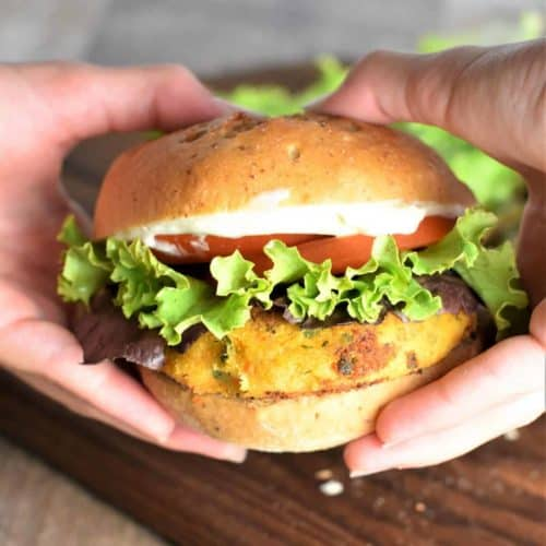 Veggie burger on a bun with lettuce tomatoes and mayo being held by hands