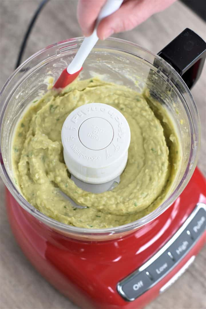 Scraping the sides of a food processor with a spatula