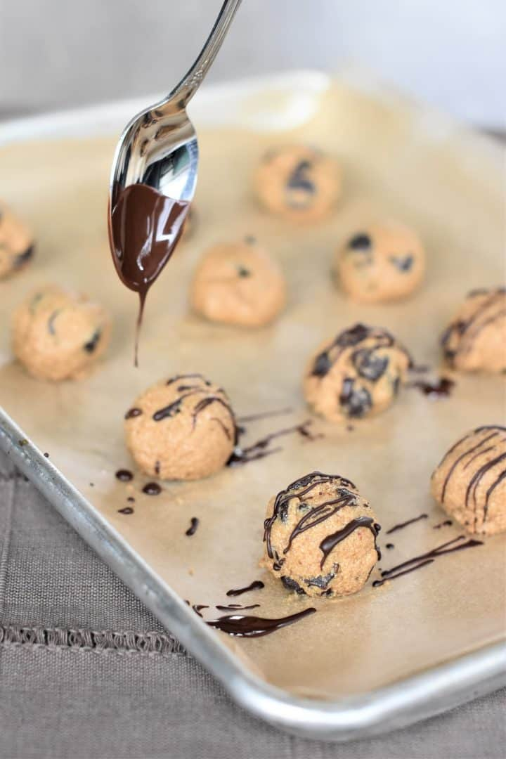 Melted chocolate being drizzled on cookie dough balls