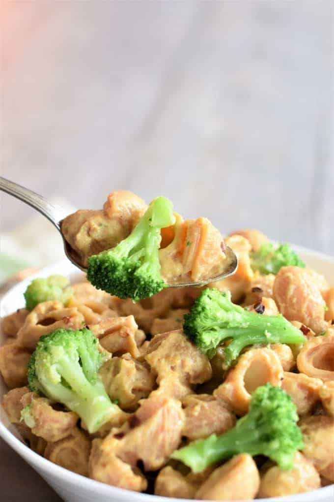 Spoonful of vegan mac and cheese with broccoli