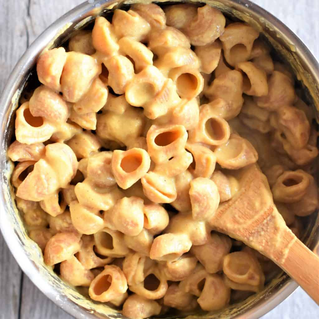 Mac and Cheese in a pan with a wooden spoon