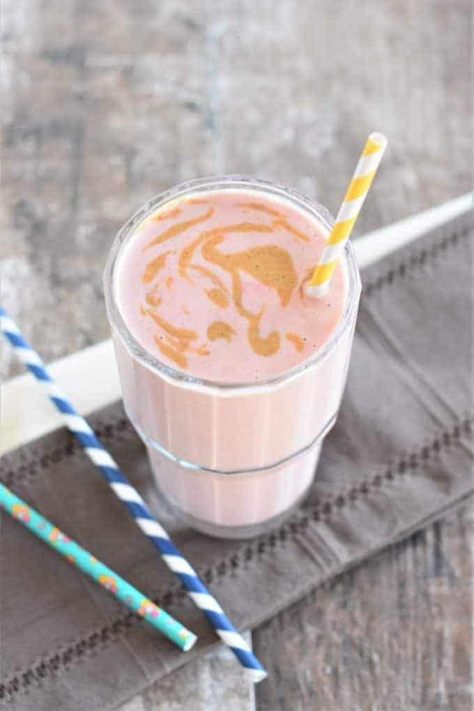 Strawberry-Banana Peanut Butter Smoothie in a glass with peanut butter swirl on top