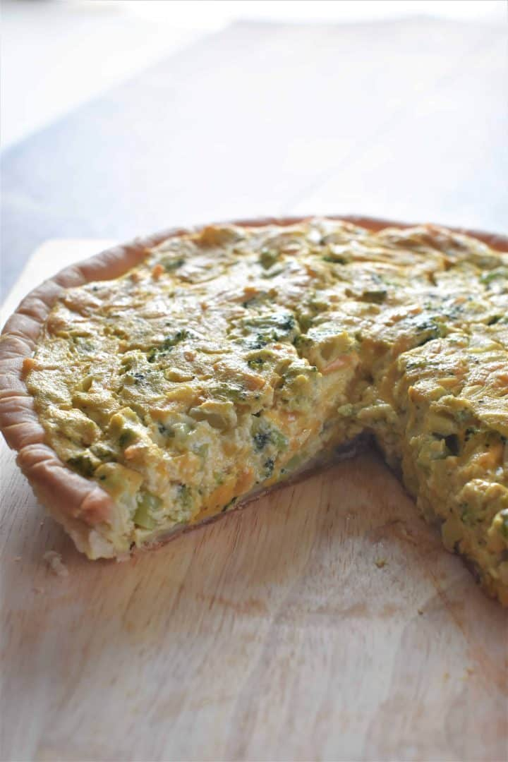 Cheesy Broccoli Vegan Quiche on wooden cutting board