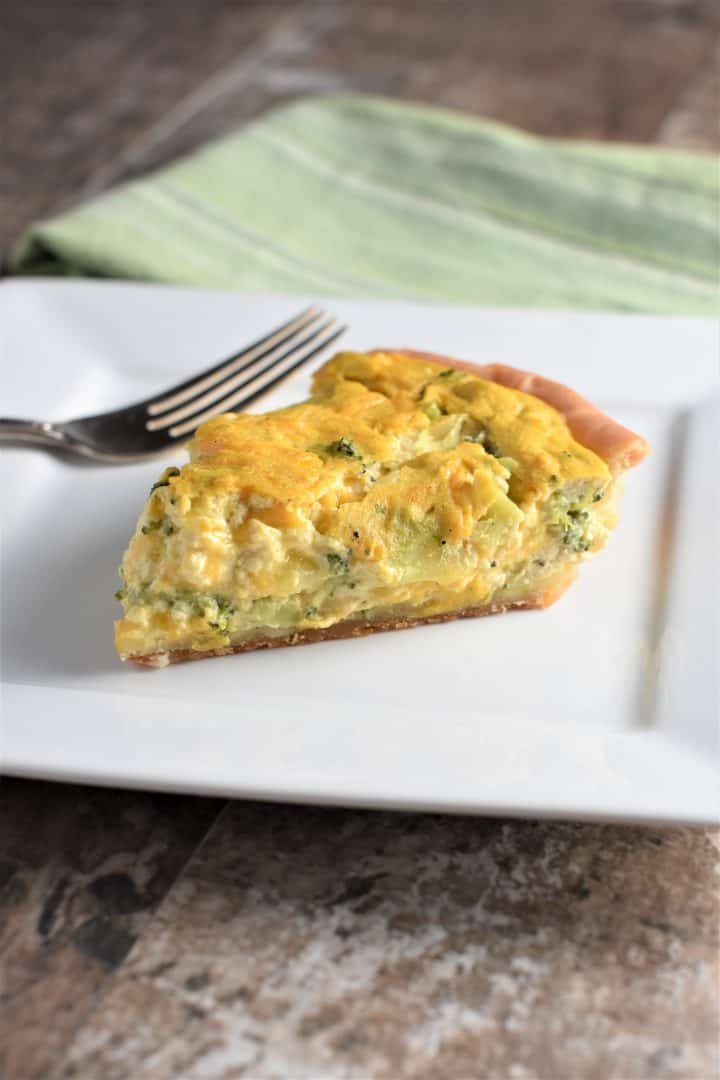 Cheesy Broccoli Vegan Quiche on a plate with a fork