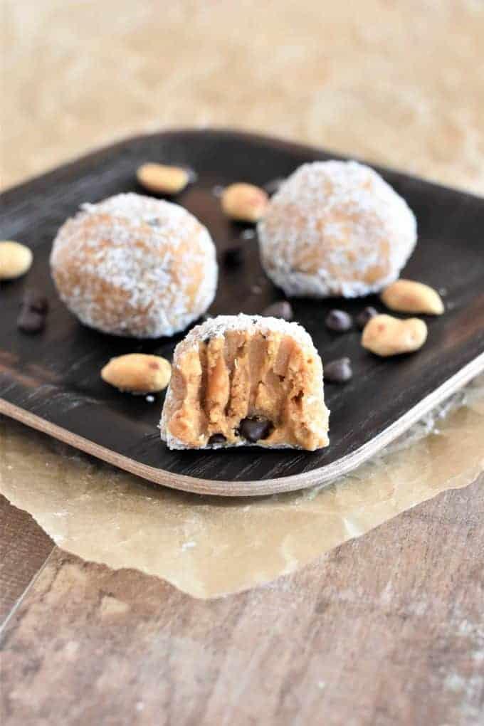 Bitten peanut butter balls on a wooden plate