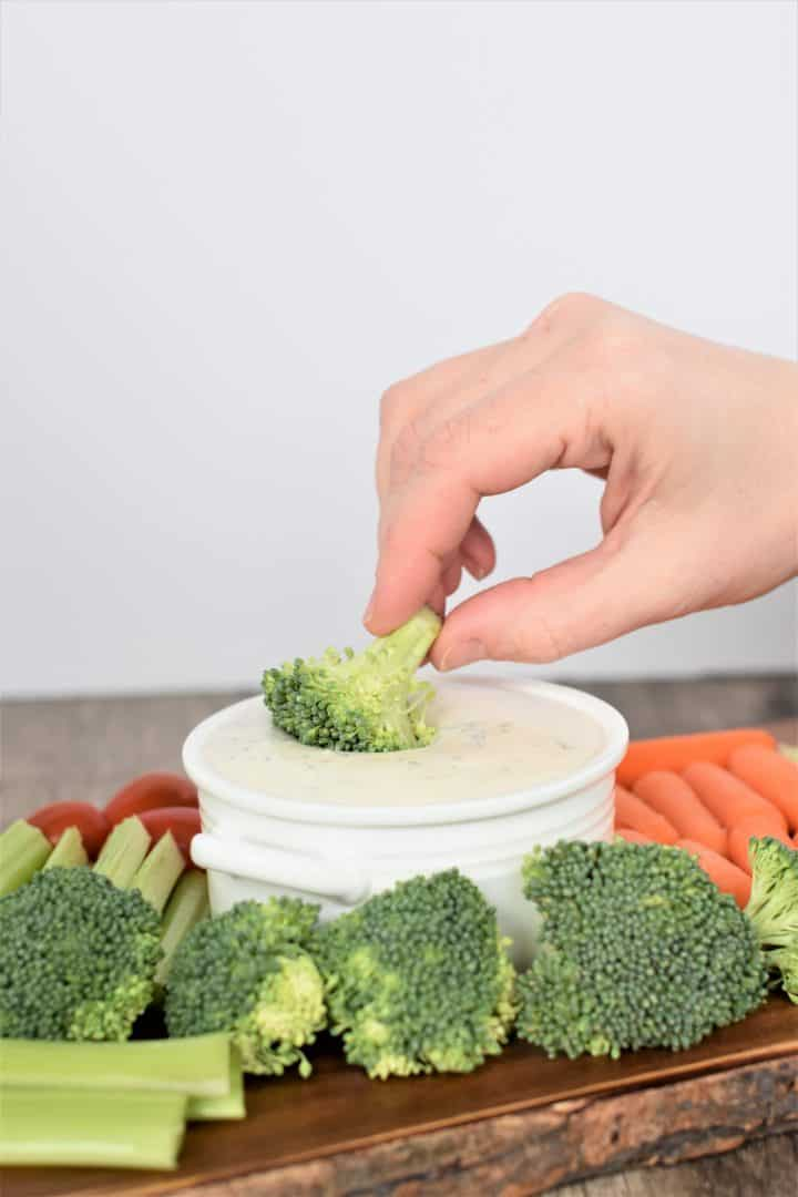 Dipping broccoli into vegan ranch dressing