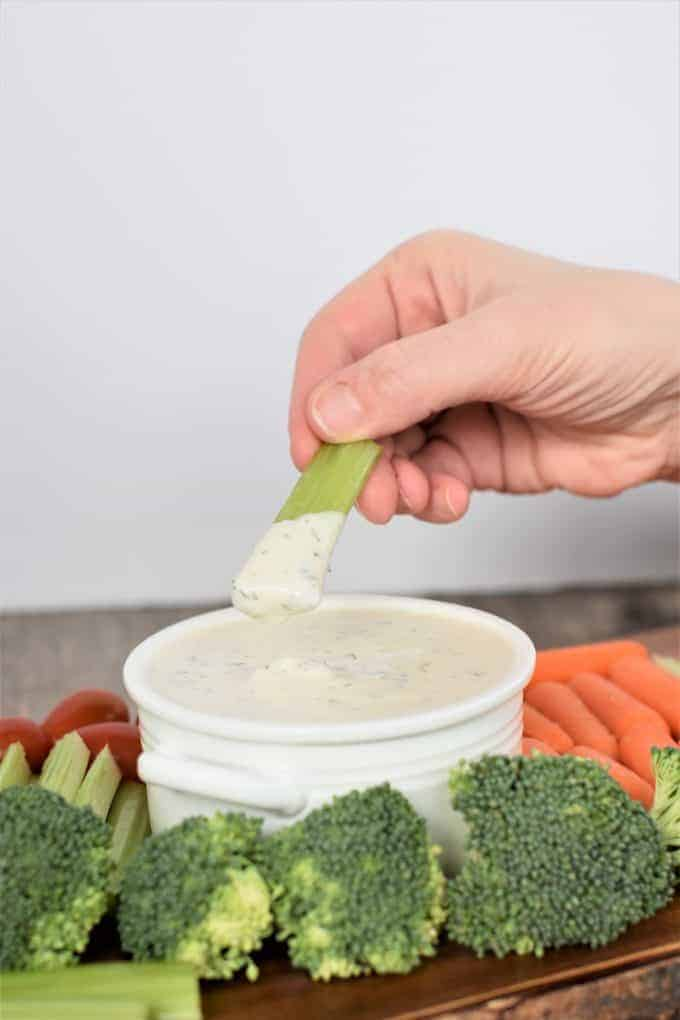 Dipping celery into vegan ranch dressing