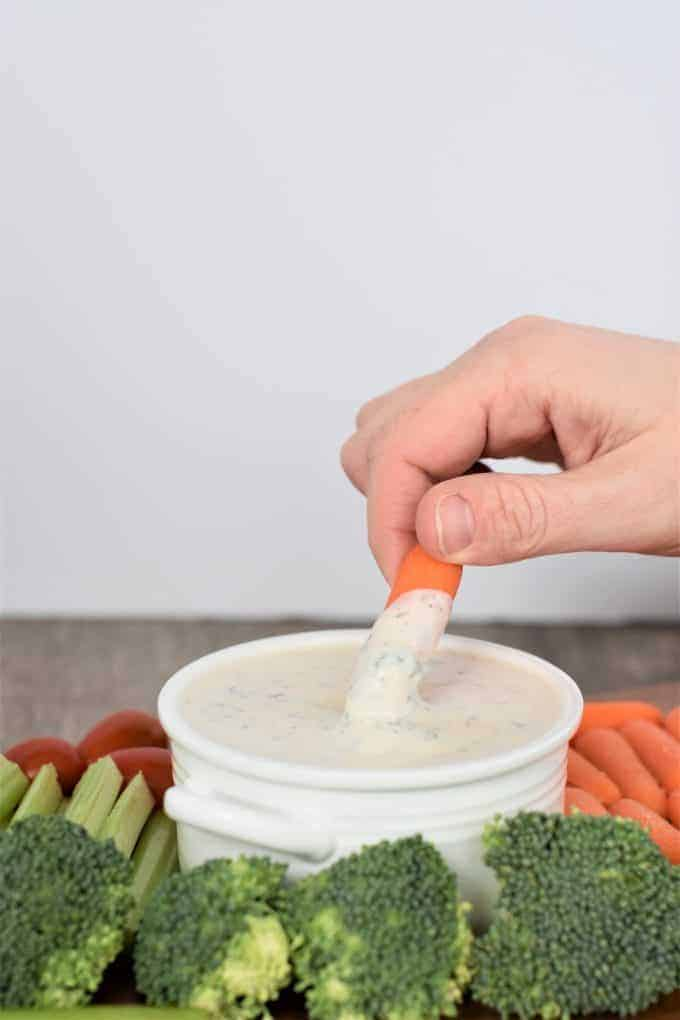 Dipping a carrot into vegan ranch dressing