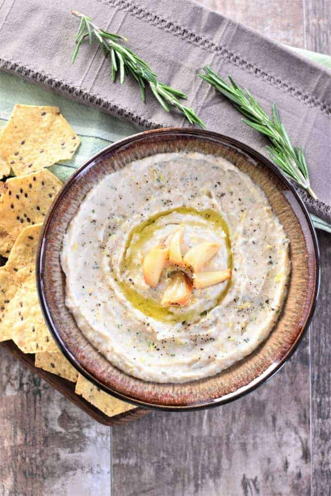 Roasted Garlic White Bean Dip in a bowl with garlic and oil on top