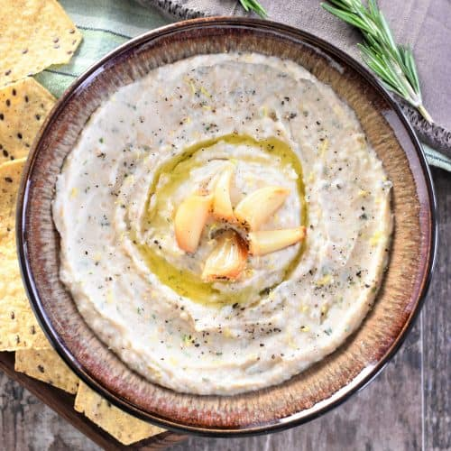 Roasted Garlic White Bean Dip in a bowl with garlic on top