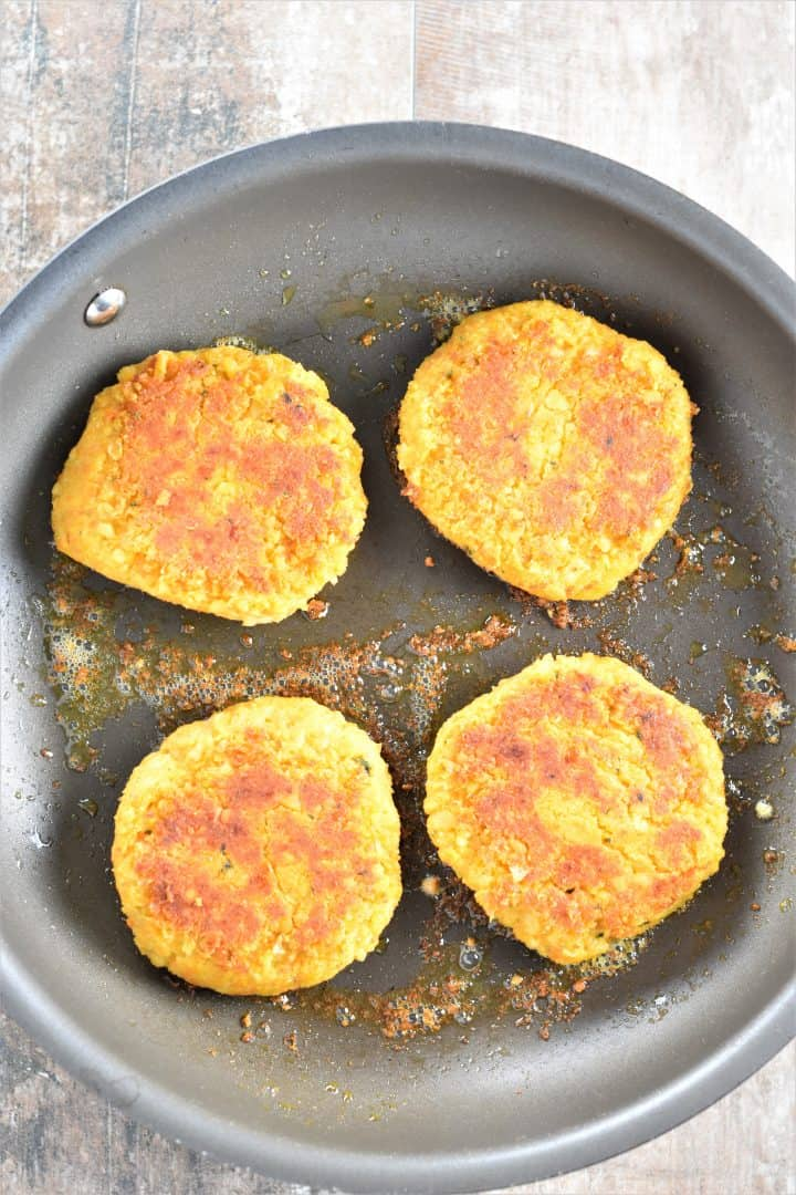 Chickpea burger patties cooking in a pan
