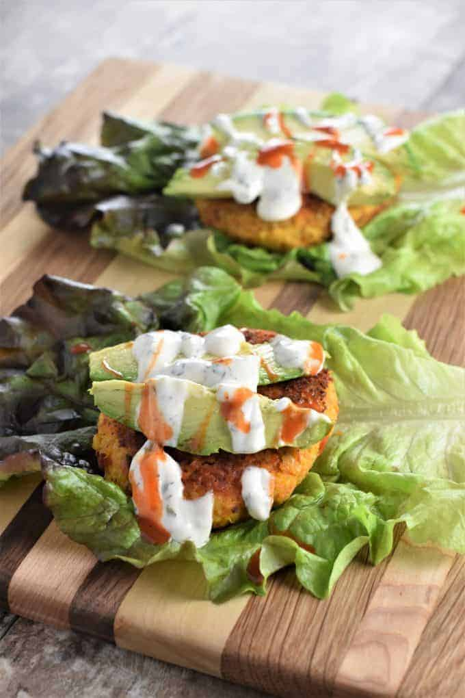 Vegan Buffalo Chickpea Burgers on lettuce with ranch dressing