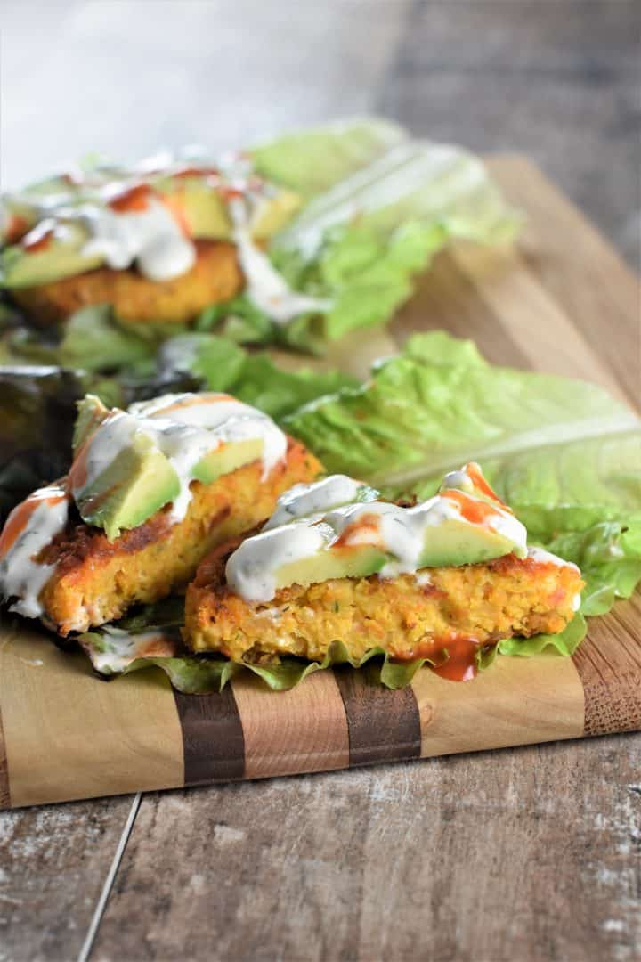 Vegan Buffalo Chickpea Burgers on lettuce with ranch dressing and avocado