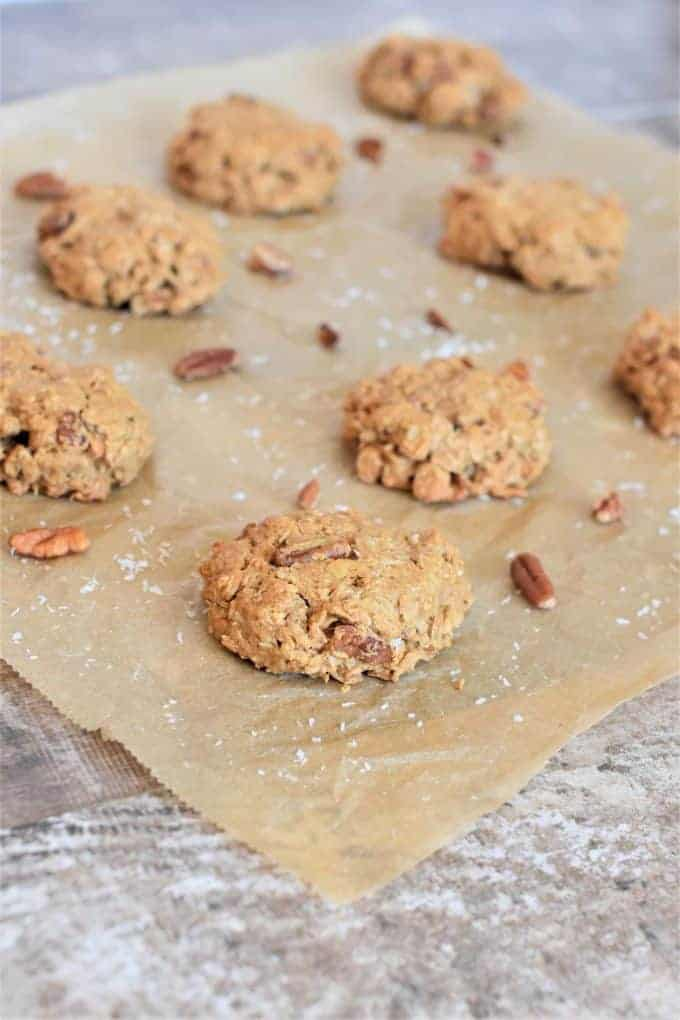 Oat Flour Cookies on parchment paper with coconut and pecans