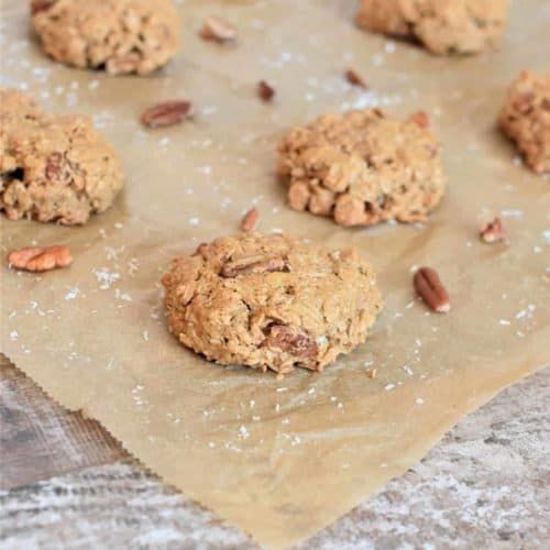 Cookies on parchment paper with pecans and shredded coconut