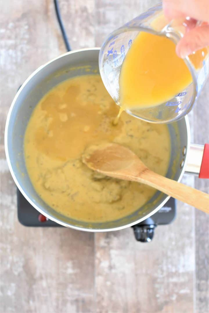 Vegetable broth being poured into saucepan