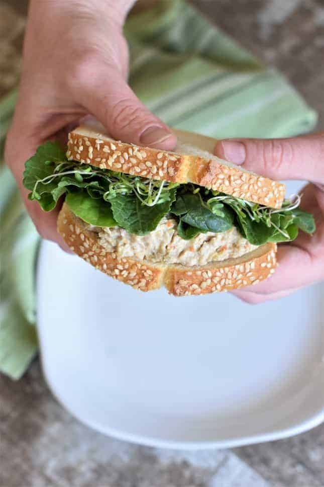 Holding a chickpea salad sandwich
