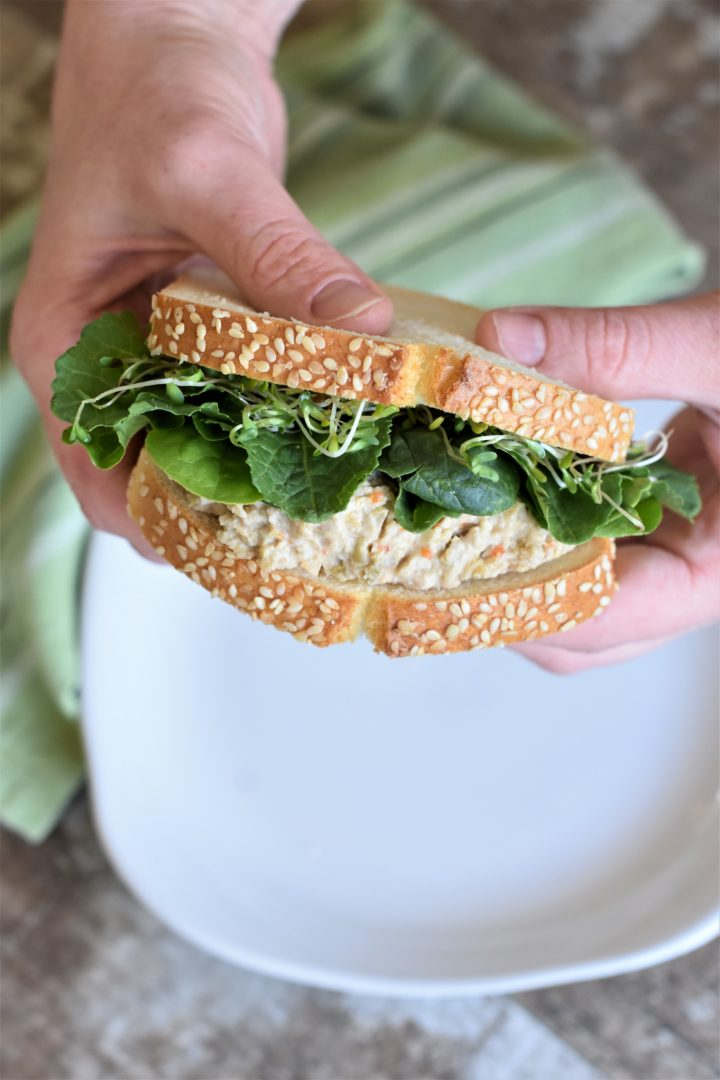 Holding a sandwich with two hands over a plate