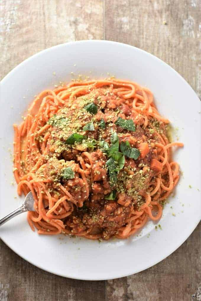 Bolognese sauce served over sweet potato noodles topped with vegan parmesan cheese