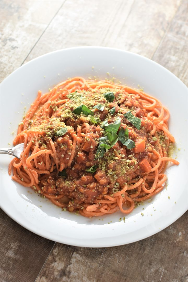 Sauce served over sweet potato noodles topped with vegan parmesan