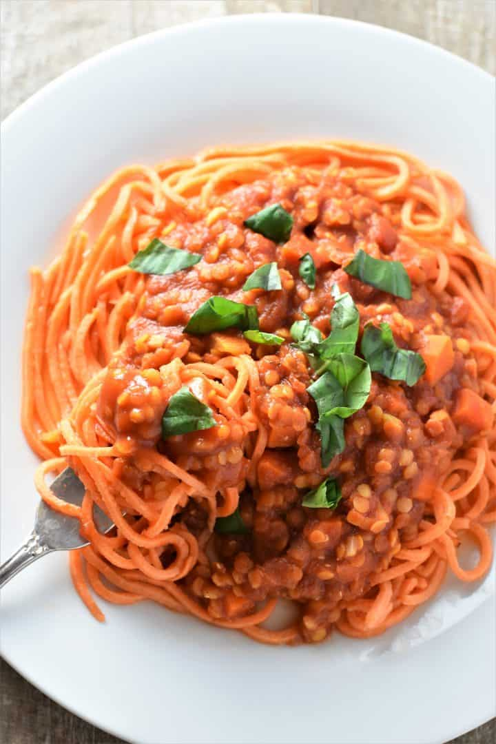 Bolognese sauce served over sweet potato noodles with a fork