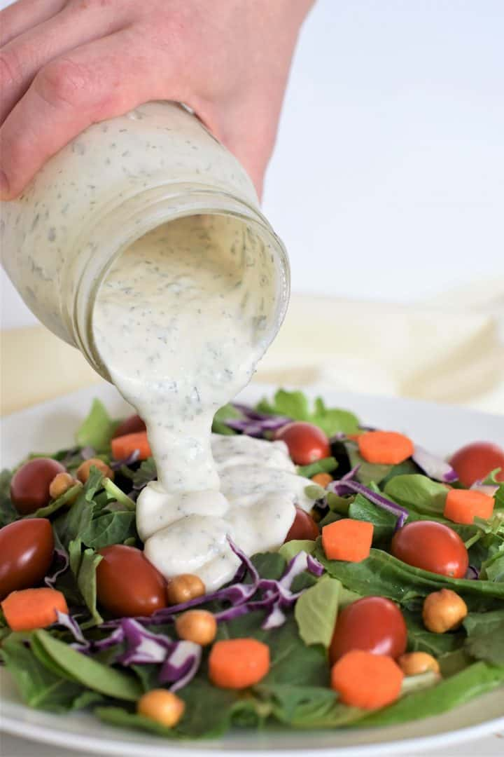 Ranch dressing being poured on a salad from a mason jar